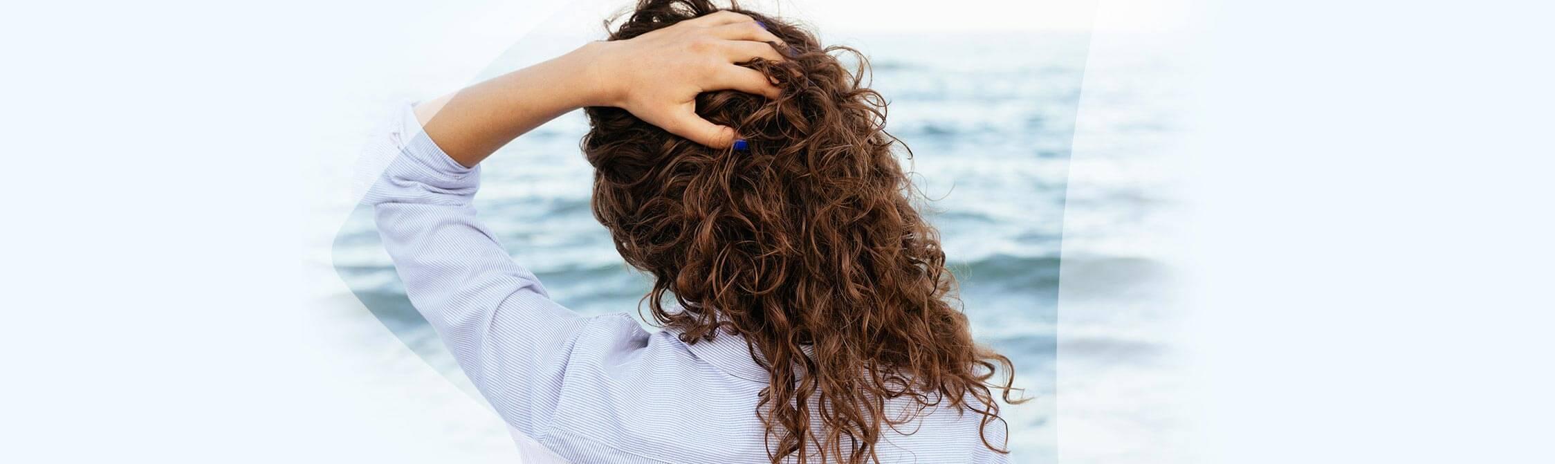 Vrouw met de handen in het haar kijkt over de zee uit