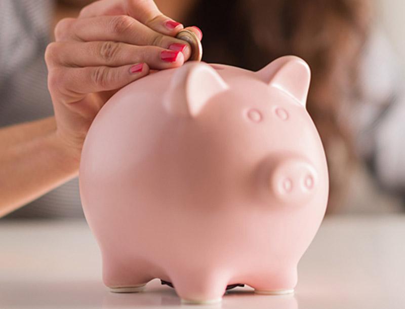 Vrouw steekt muntstuk in spaarvarken