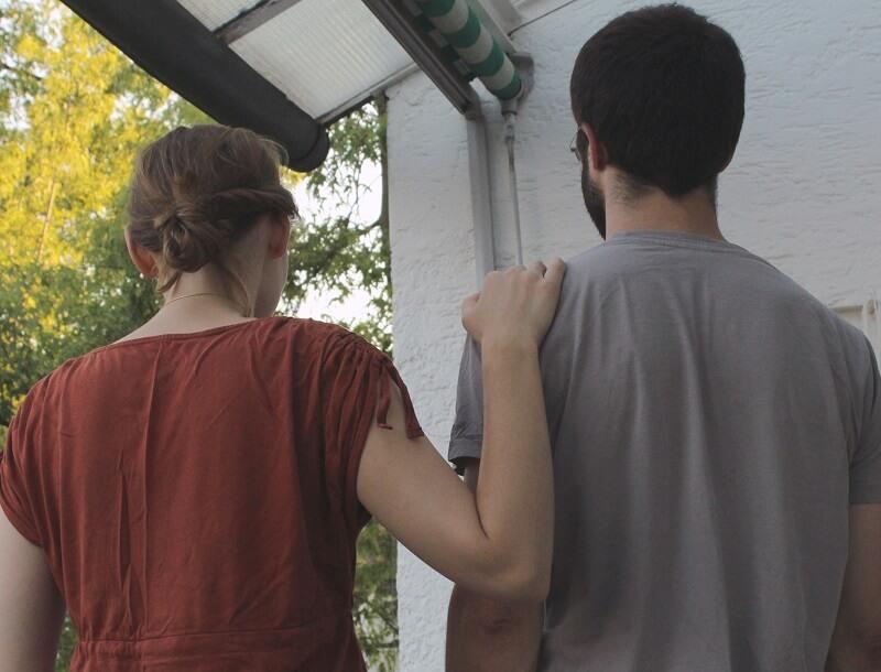 Vrouw legt hand op de schouder van een man